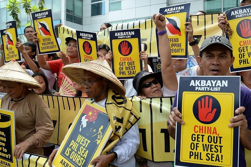 Protesters hold anti-China placards and shout slogans during a rally in front of the building housing Chinese consular offices in Manila on April 2, 2014. -- PHOTO: AFP