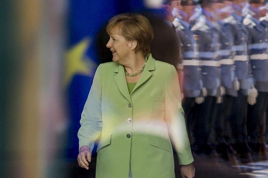 Honour guards are reflected on a window as German Chancellor Angela Merkel arrives to meet Tunisia's Prime Minister Mehdi Jomaa (not pictured) at the Chancellery in Berlin on June 18, 2014.German Chancellor Angela Merkel said on Wednesday, June