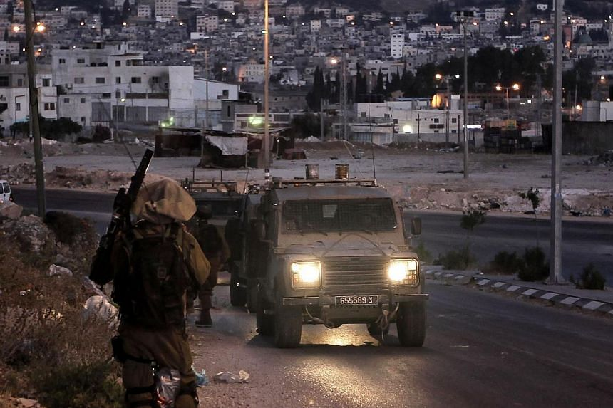 Israeli soldiers take part in a search operation for three Israeli teenagers believed kidnapped by Palestinian militants, early on June 18, 2014 in the West Bank town of Nablus.Israeli troops arrested 65 Palestinians overnight, most of wh