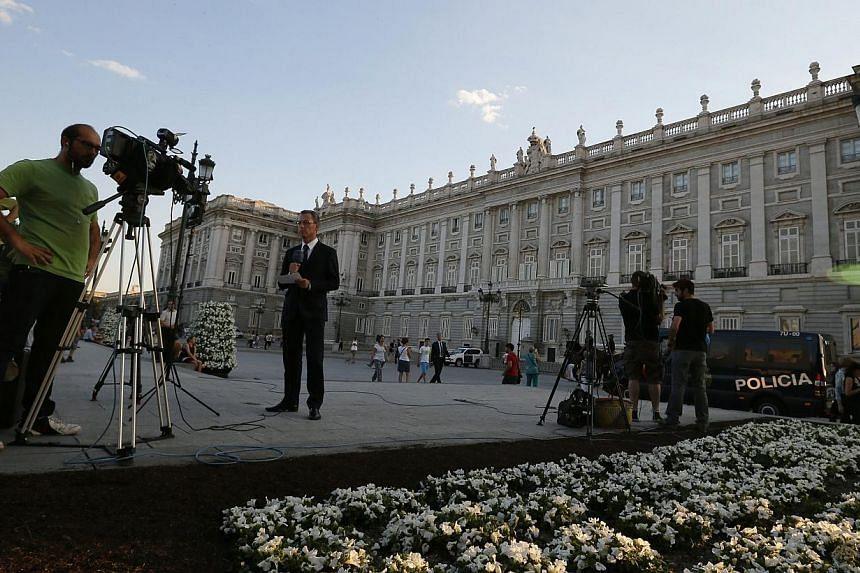 Journalists work as police officers patrol outside the Royal Palace in Madrid on June 17, 2014.Spain's King Juan Carlos signs an act of abdication on Wednesday, June 18, 2014, to end his 39-year reign, as a flag-festooned Madrid spruces up its
