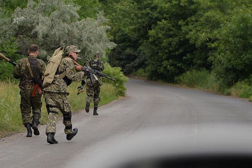 Pro-Russian armed militiamen take up positions on a secondary road between Kramatorsk and Slavyansk, on June 11, 2014. -- PHOTO: AFP