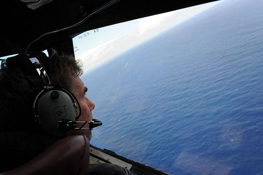 In this file photo taken on April 13, 2014 from a Royal New Zealand Airforce (RNZAF) P-3K2-Orion aircraft, co-pilot and Squadron Leader Brett McKenzie helps to look for objects during the search for missing Malaysia Airlines flight MH370, off Perth.&