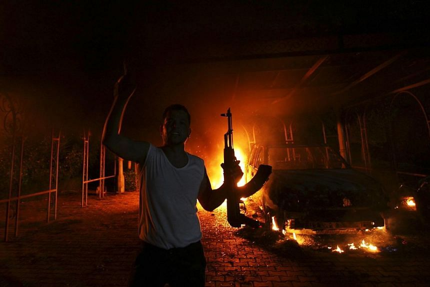 A protester reacts as the U.S. Consulate in Benghazi is seen in flames during a protest by an armed group said to have been protesting a film being produced in the United States in this Sept 11, 2012 file photo.US commandos have captured the su