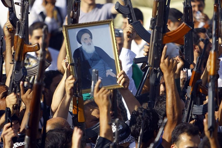 Iraqi Shiite tribesmen brandish their weapons and a poster of Shiite cleric Grand Ayatollah Ali al-Sistani as they gather to show their willingness to join Iraqi security forces in the fight against Jihadist militants who have taken over several nort
