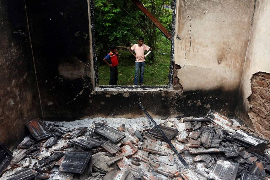 Muslim boys stand next to a burnt house after clashes between Buddhists and Muslims in Aluthgama on June 16, 2014. At least three Muslims were killed and 75 people seriously injured in violence between Buddhists and Muslims in southern Sri Lankan coa