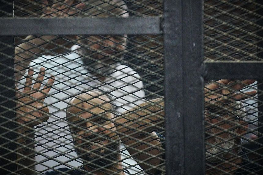 Egypt's Muslim Brotherhood members Mohammed al-Baltaci (top), Khairat al-Shater (left) and Mohamed Badie (right) stand behind the defendants cage during the trial of 23 people charged over the September killing of police general Nabil Farrag in Kerda