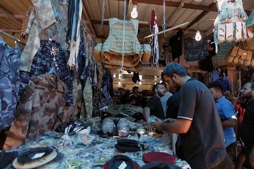 Iraqi men buy military uniforms at a shop in Baghdad, on June 17, 2014.Sunni militants attacked Iraq's largest oil refinery, located in Baiji in northern Iraq, with machine-gun fire and mortars on Wednesday, Iraqi security sources and refinery