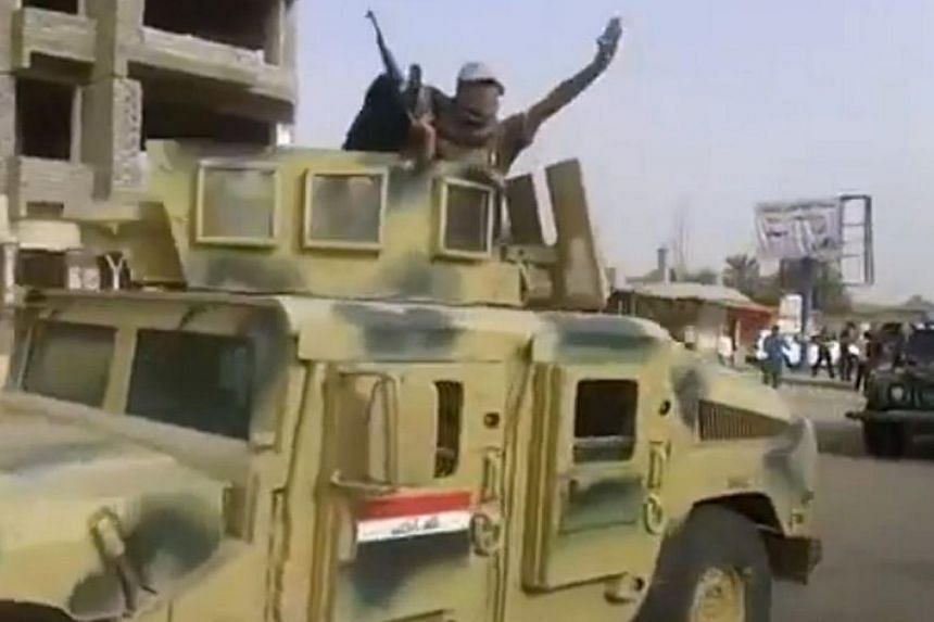 An image grab taken from a video uploaded on Youtube on June 17, 2014, allegedly shows militants from the Islamic State of Iraq and the Levant (ISIL) parading with an Iraqi army vehicle in the northern city of Baiji in the in Salaheddin province.&nbs
