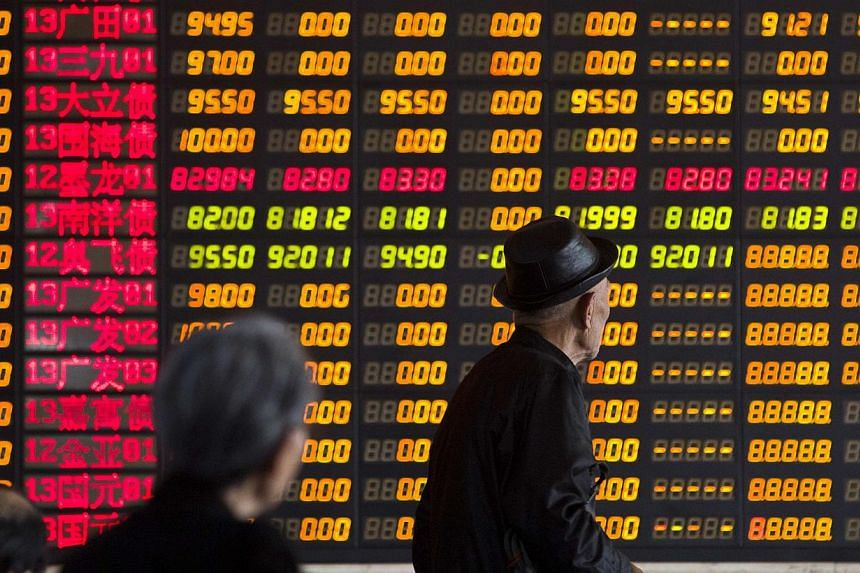 Caption: Investors look at information displayed on an electronic screen at a brokerage house in Shanghai, April 14, 2014. China shares were flat in light trade on Wednesday morning. -- PHOTO: REUTERS