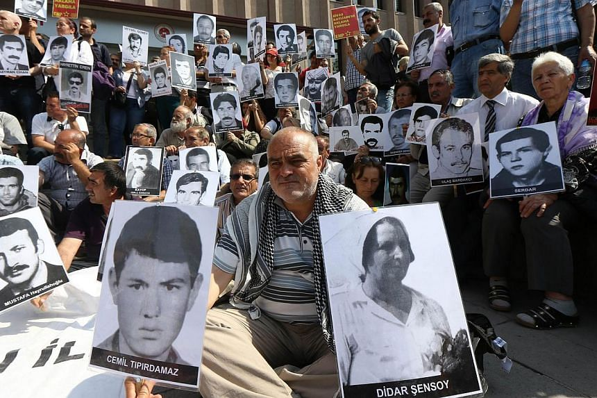 Turkish leftist demonstrators hold pictures of people who were executed or died in jail during the military rule that followed the 1980 coup in Turkey, in front of a courthouse in Ankara on June 18, 2014.A Turkish court on Wednesday handed life