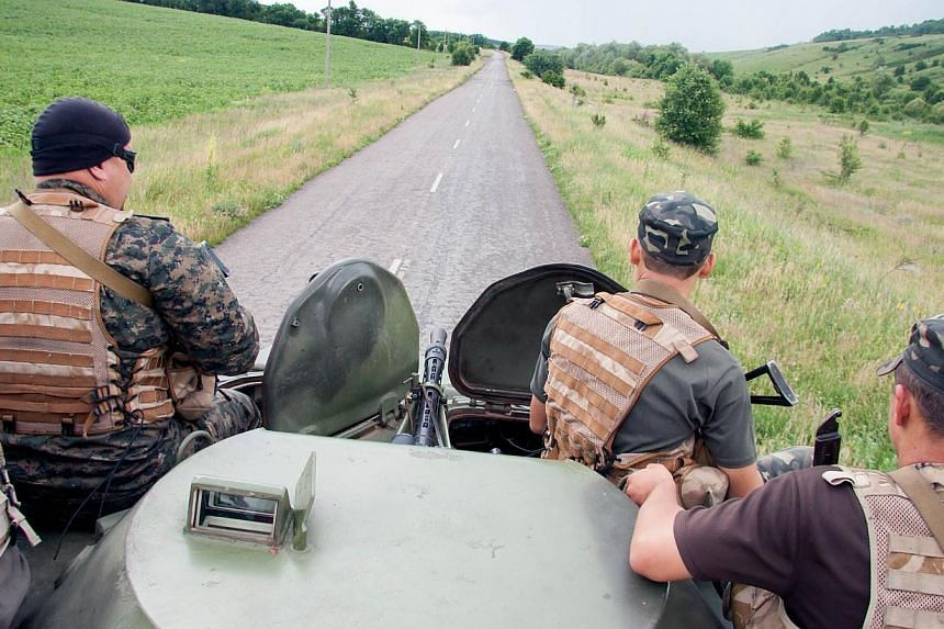 Ukrainian troops patrol an area near the border of Ukraine with Russia outside Kharkiv on June 16, 2014. Ukraine's new President Petro Poroshenko said on Wednesday that he will soon order a unilateral ceasefire in the separatist east as part of