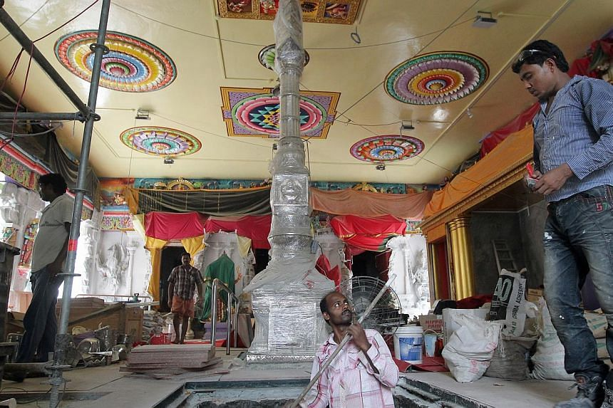 Workers seen inside the main hall of the Sri Veeramakaliamman temple along Serangoon Road during renovation and restoration works on May 30, 2014. Several roads and lanes are to be closed to vehicles in view of a consecration ceremony by the Sri