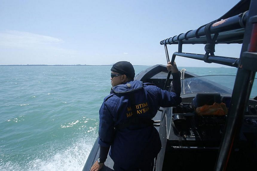 A Malaysia Maritime officer looks out into the sea during a search and rescue in Kuala Langat outside Kuala Lumpur, off Malaysia's western coast on June 18, 2014. -- PHOTO: REUTERS