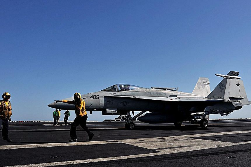 In this image released by the US Navy, sailors direct an F/A-18C Hornet on the flight deck of the aircraft carrier USS George H.W. Bush during flight operations in the Arabian Gulf on June 17, 2014. -- PHOTO: AFP