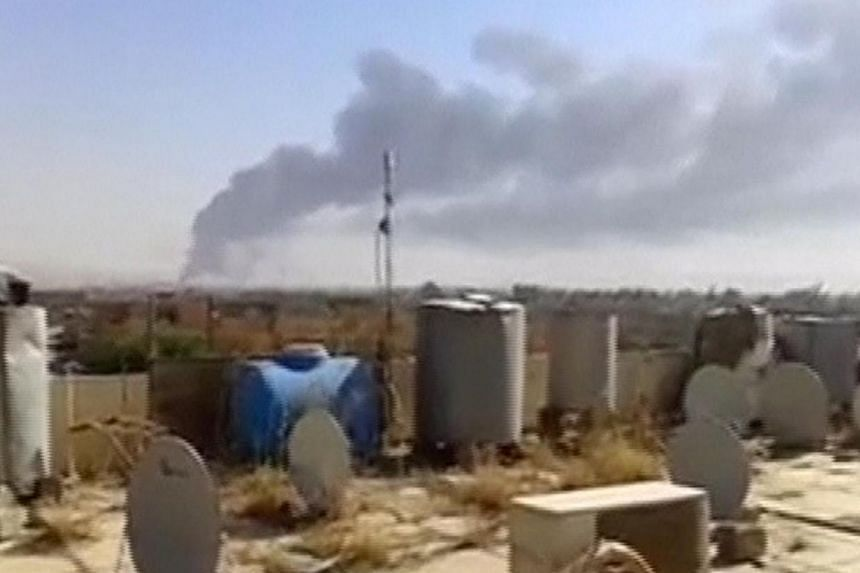A large plume of smoke rises from what is said to be Baiji oil refinery in Baiji, northern Iraq, in this still image taken from an amateur video posted on a social media website June 18, 2014.Iraqi government forces regained full control on Thu