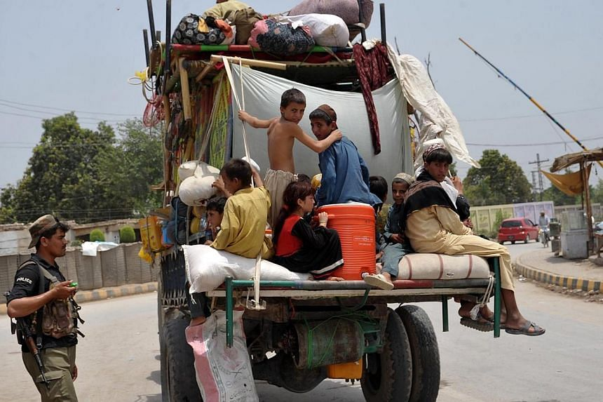 Pakistani civilians, fleeing from a military operation in North Waziristan tribal agency, cross a checkpoint as they arrive in Bannu district on June 19, 2014.Civilians are streaming out of a Pakistani tribal area in a two-pronged exodus ahead
