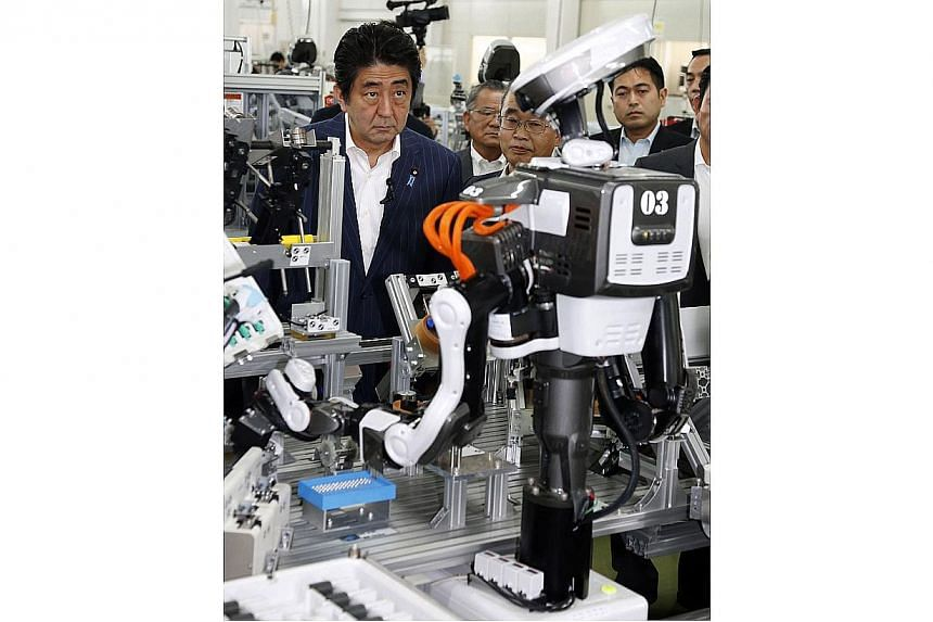 """Japanese Prime Minister Shinzo Abe inspects a robot working at an assembly line of cash dispensers at a factory in Kazo, suburban Tokyo on June 19, 2014.Japanese Prime Minister Shinzo Abe wants to stage a """"Robot Olympics"""" in 2020, the same year"""