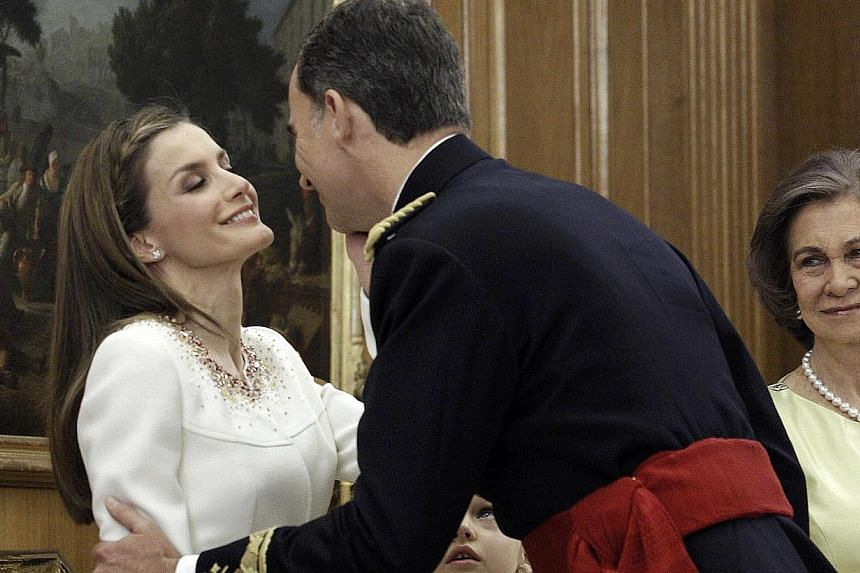 Spain's new King Felipe VI (centre), wearing the Sash of Captain-General, kisses his wife Queen Letizia as his mother Queen Sofia (right) looks on during a ceremony at La Zarzuela Palace in Madrid on June 19, 2014. -- PHOTO: REUTERS