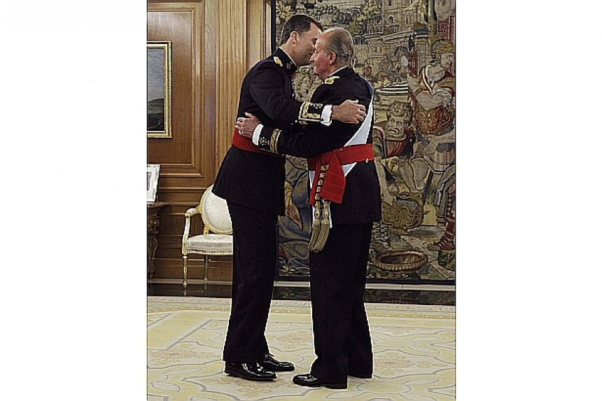 Spain's King Juan Carlos (right) and new King Felipe VI embrace after the placing of the Sash of Captain-General during a ceremony at La Zarzuela Palace in Madrid on June 19, 2014. -- PHOTO: REUTERS