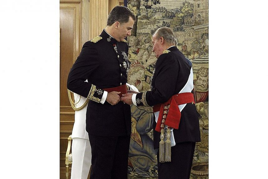 Spain's King Juan Carlos (right) places the Sash of Captain-General on new King Felipe VI during a ceremony at La Zarzuela Palace in Madrid on June 19, 2014. -- PHOTO: REUTERS