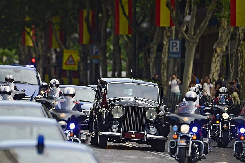 Spain's King Felipe VI, Spain's Queen Letizia and Spanish Crown Princess of Asturias Leonor ride in a vehicle on the way from the Zarzuela Palace to the Congress of Deputies, Spain's lower House, in Madrid on June 19, 2014, for a swearing-in ceremony