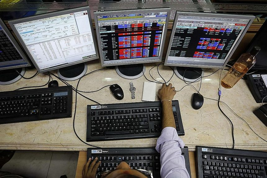 A broker monitors share prices while trading at a brokerage firm in Mumbai on May 13, 2014.India's capital market regulator said the government should dilute its stake in listed public-sector companies over the next three years and cap it at 75