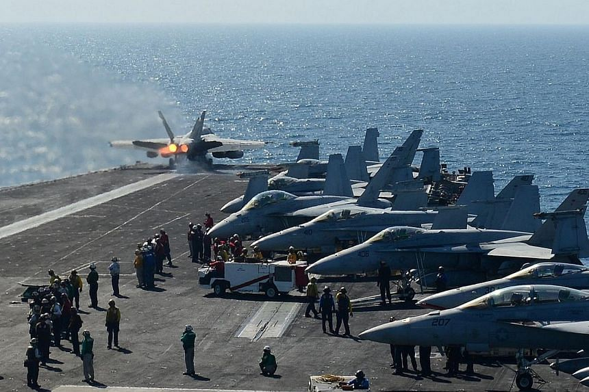 In this image released by the US Navy, a plane launches off the flight deck of the aircraft carrier USS George H.W. Bush during flight operatuions in the Arabian Gulf on June 17, 2014.The United States is flying F-18 attack aircraft launched fr