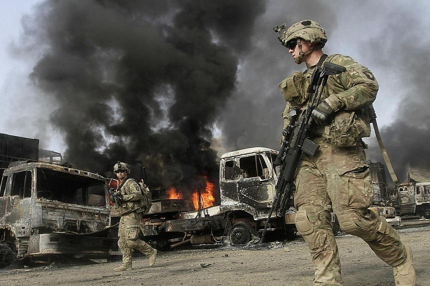 Nato troops walk near burning Nato supply trucks after, what police officials say, was an attack by militants in the Torkham area near the Pakistani-Afghan in Nangarhar Province on June 19, 2014.Four Taleban militants struck a Nato post in the