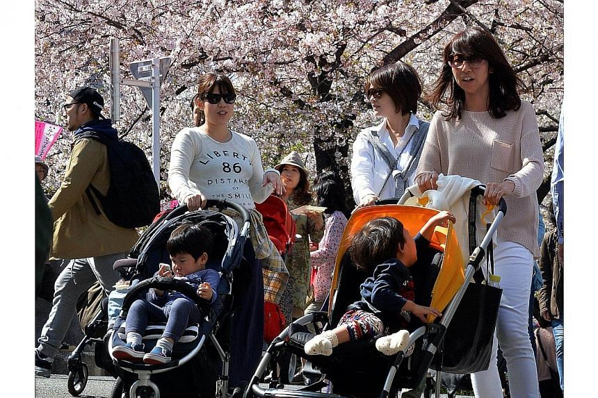 Young mothers push their baby strollers under fully bloomed cherry blossom trees along a riverside promenade in Tokyo on April 4, 2014.Sexist jeers from governing party members on Thursday, June 19, 2014, repeatedly interrupted a Tokyo assembly