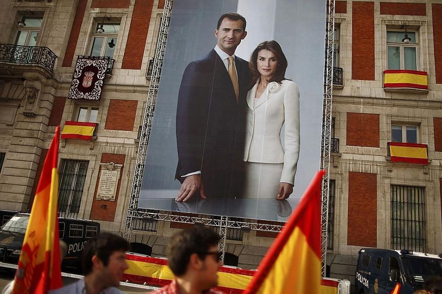 People holding Spanish flags walk past a picture showing Spain's new King Felipe VI and his wife Queen Letizia hanging on a buiding's facade, downtown Madrid, on June 19, 2014. -- PHOTO: REUTERS