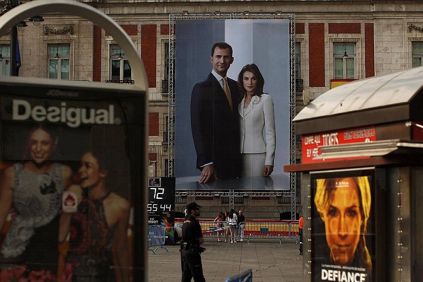 A picture showing Spain's new King Felipe VI and his wife Queen Letizia hangs on a buiding's facade, downtown Madrid, on June 19, 2014. -- PHOTO: REUTERS