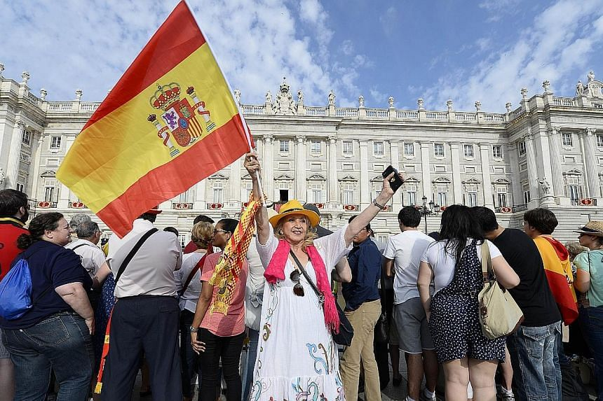 A woman waves a Spanish flag outside the Palacio de Oriente or Royal Palace in Madrid on June 19, 2014, before a swearing in ceremony of Spain's new King. -- PHOTO: AFP