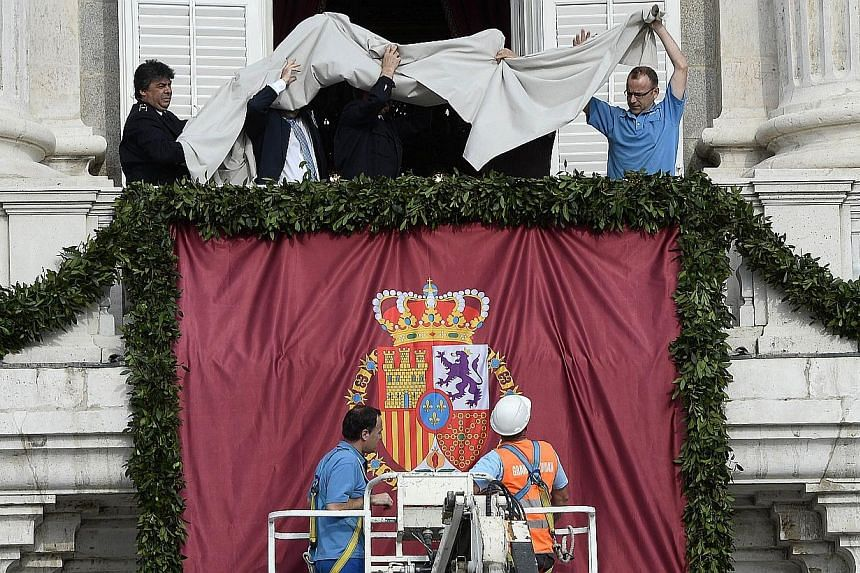 Workers remove a cover revealing a Spanish coat of arms flag on the central balcony of the Palacio de Oriente or Royal Palace in Madrid on June 19, 2014, before a swearing in ceremony of Spain's new King. -- PHOTO: AFP