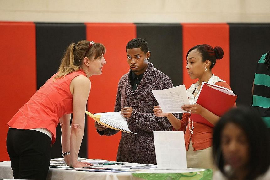 Ms Wendy Larsen (left) speaks to candidates at a job fair in Chicago, Illinois, on June 12, 2014. New US claims for unemployment insurance benefits fell last week, continuing to point to a downward trend in job losses, official data released on June