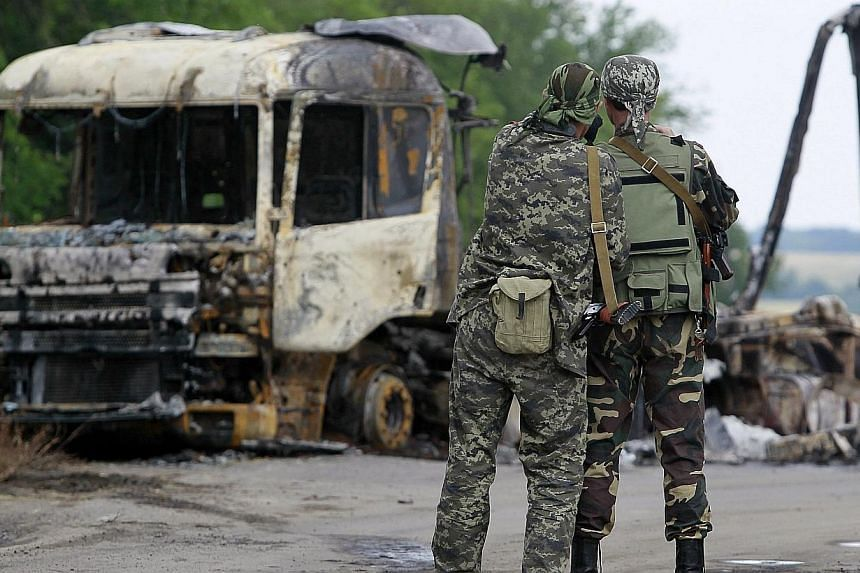 Pro-Russian separatists stand guard at a checkpoint near a burnt truck outside Luhansk on June 18, 2014.Ukrainian forces and pro-Russian separatists were locked in a fierce battle in the rebellious east of the country on Thursday, June 19, 2014