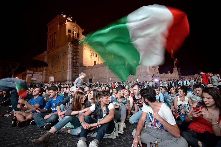 Italian fans celebrate their team's victory over England in the 2014 World Cup as they watch the match on a large screen in central Rome's Piazza Venezia on June 14, 2014. -- PHOTO: AFP
