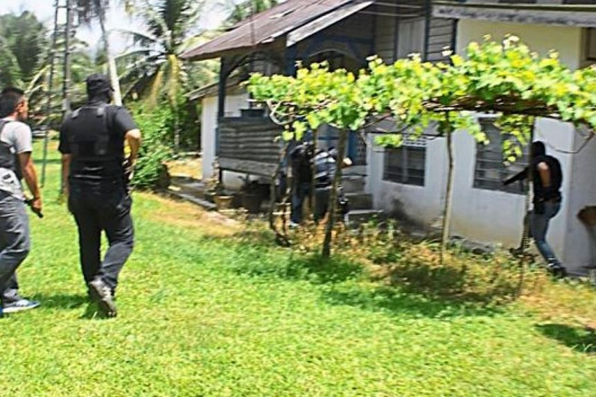 Members of Bukit Aman Counter Terrorism Division detaining a man after raiding his home in Kampung Kelebor in Kuala Kangsar. The 25-year-old man is believed to be the weapons handler for a militant group linked to the group waging wars in Syria and I