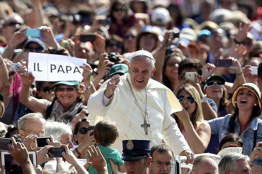 Pope Francis waves as he arrives at his weekly general audience at St. Peter's Square at the Vatican June 18, 2014. -- PHOTO: REUTERS
