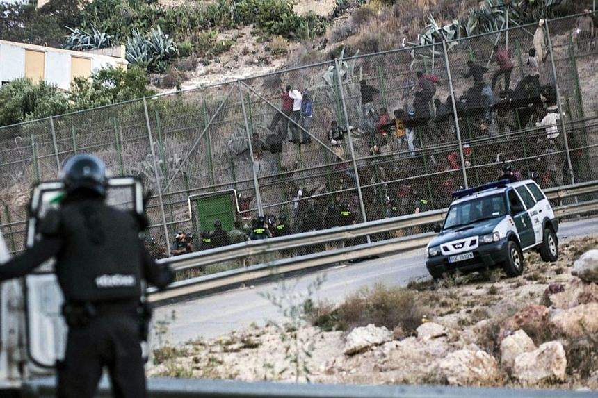Would-be immigrants try to scale a boarder fence separating Morocco from the Spanish enclave of city of Melilla on June 18, 2014. Some 400 sub-Saharan migrants tried today unsuccessfully to enter Melilla with some 150 still stuck on the fence itself
