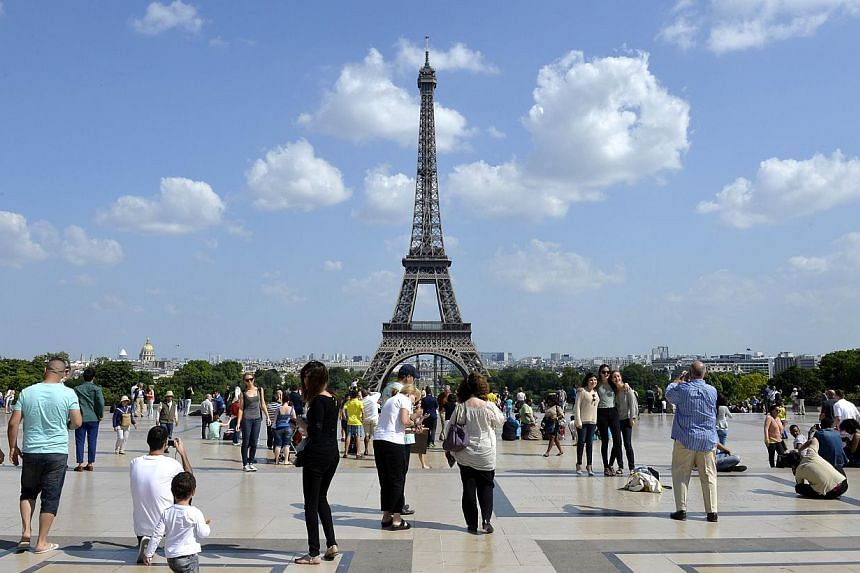 People stand and take photographs at the Human Rights Square in front of the Eiffel tower on a warm and sunny day on June 18, 2014 in Paris. -- PHOTO: AFP
