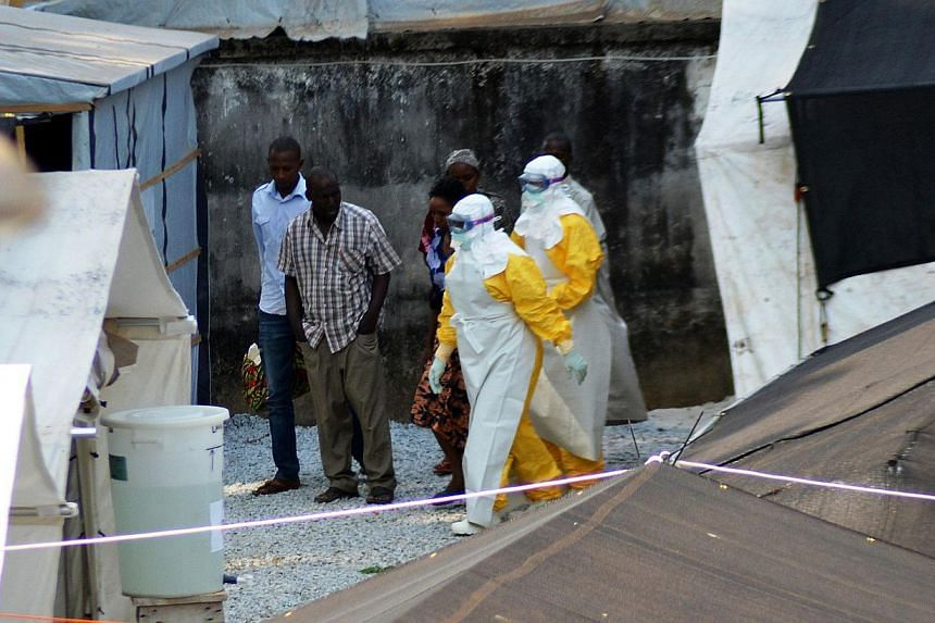 A file photo taken on April 14, 2014 shows health workers, wearing protective suits, walking in an isolation center for people infected with Ebola at Donka Hospital in Conakry. -- PHOTO: AFP