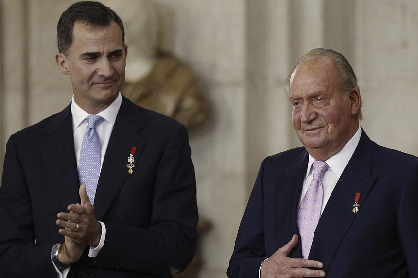 Spain's former king Juan Carlos (right) reacts next to his son Felipe during the signature ceremony of the act of abdication at the Royal Palace in Madrid on June 18, 2014. -- PHOTO: REUTERS