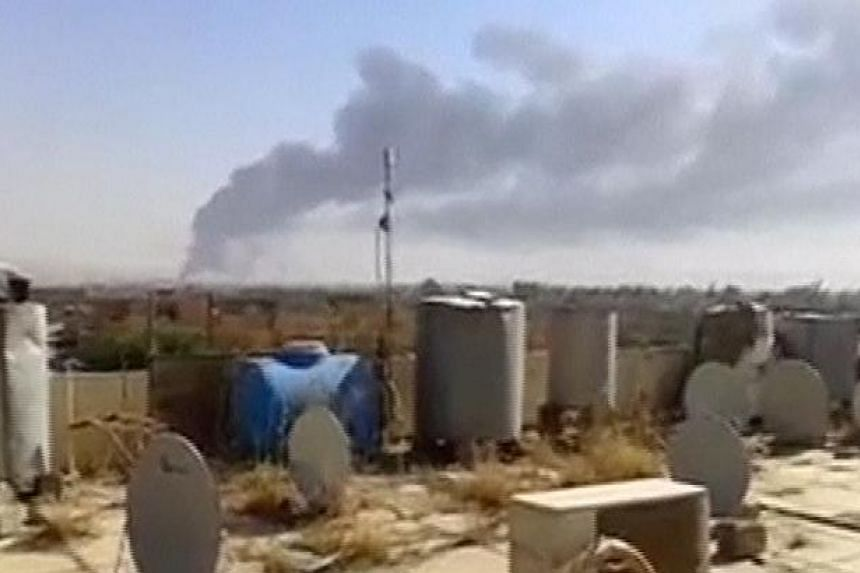 A large plume of smoke rises from what is said to be Baiji oil refinery in Baiji, northern Iraq, in this still image taken from an amateur video posted on a social media website June 18, 2014. -- PHOTO: REUTERS
