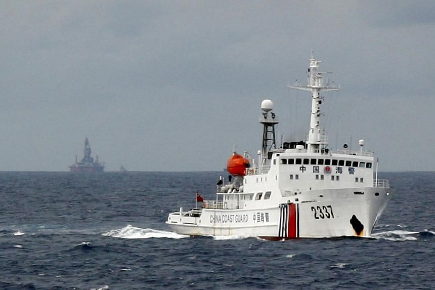 """A Chinese Coast Guard vessel (R) passes near the Chinese oil rig, Haiyang Shi You 981 (L) in the South China Sea, about 210 km from the coast of Vietnam on June 13, 2014. The Philippines said China's """"expansion agenda"""" in the disputed South Chi"""