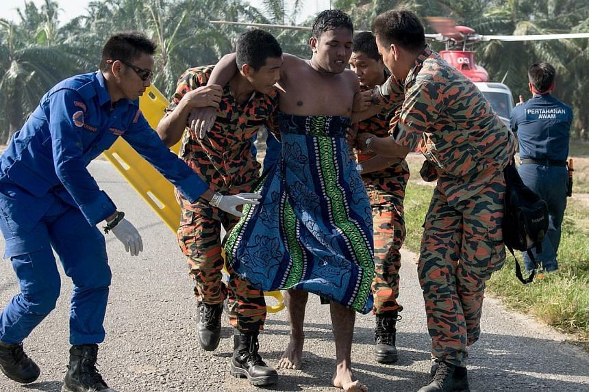 A Malaysian search and rescue team helps a rescued victim (centre) from a capsized boat in Kelanang Jetty, near Banting after an apparently overloaded boat carrying Indonesian illegal migrants sank in seas off western Malaysia on June 19, 2014. -- PH