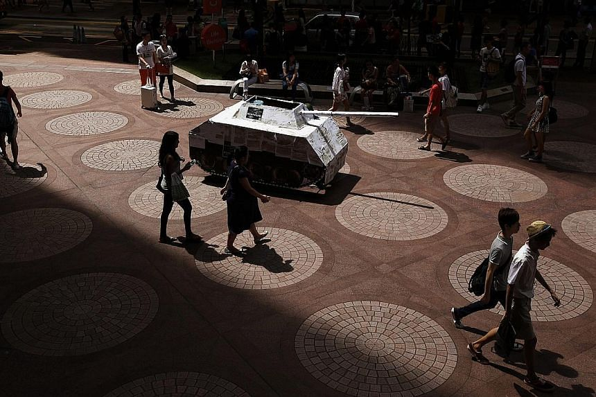 """A mock tank, covered with photocopies of the """"One country, two systems"""" white paper released earlier by Beijing on Hong Kong's control, is displayed by local artists to symbolise its threat to the city's autonomy, at a shopping district in Hong Kong"""