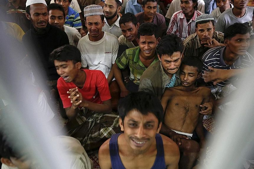 Rohingya people from Myanmar, who were rescued from human traffickers, react from inside a communal cell at Songkhla Immigration Detention Centre (IDC) where they are kept near Thailand's border with Malaysia on Feb 13, 2014.The United States S
