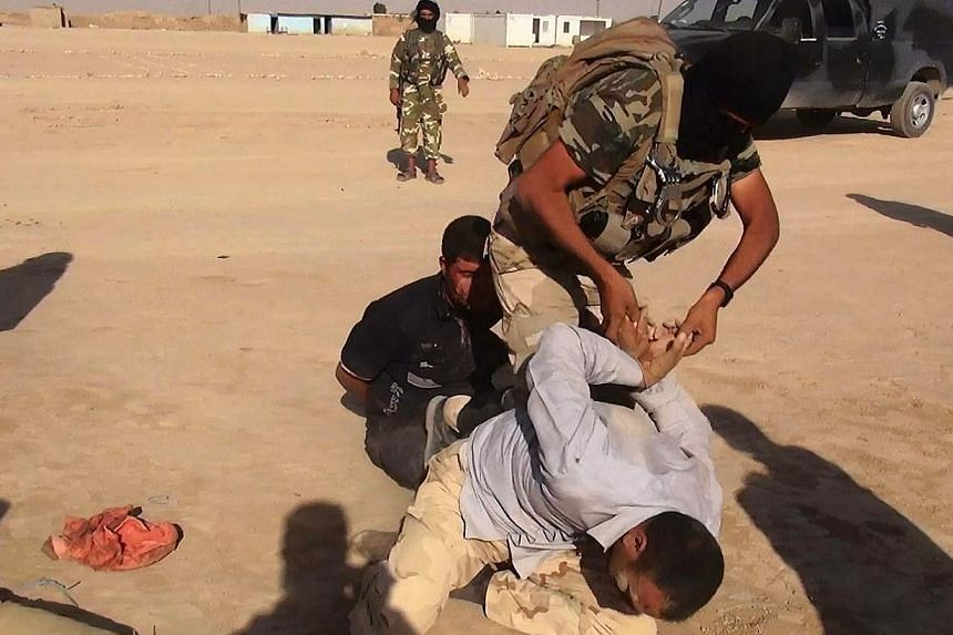 An image made available by the jihadist Twitter account Al-Baraka news on June 13, 2014 allegedly shows Islamic State of Iraq and the Levant (ISIL) militant restraining an unidentified man at an undisclosed location close to the Iraqi-Syrian border,