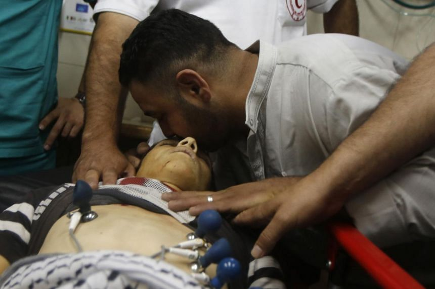 A man kissing the head of Palestinian teenager Mohammed Dudin, who medics said was killed by Israeli troops, at a hospital in the West Bank city of Hebron on Friday. PHOTO: REUTERS