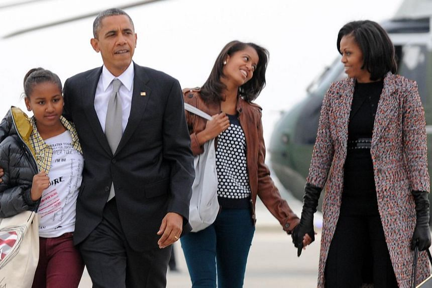 US President Barack Obama, First Lady Michelle Obama and their daughters Malia (right) and Sasha. The couple say in an interview with Parade magazine that they want their daughters to have the same experience they had of working minimum-wage jobs. &n